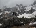 Pri balvanu nam je zmanjkalo snega. Povnova dolina je desno v megli.
